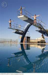 Three divers on diving boards