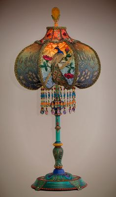 Beautiful and unusual 1920s era table lamp with peacock feather motifs has been hand painted and holds a Peacock & Roses silk and beaded shade.