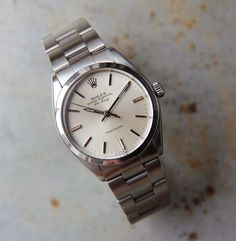 """A lovely, historically-rich, original Rolex Air King 5500/1002 series watch manufactured in 1983. One of the longest running watch series in the Rolex line, it has a distinct aeronautic pedigree in Rolex's production of professional activity watches. With its automatic movement, 34mm steel case, silver baton dial. The Rolex 78350/557 bracelet will fit a 7.5"""" wrist. A little history The Rolex Air King model dates back to the 1940's, and spans … Read More →"""