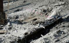 A portion of a shipwreck from the 1800s that has been uncovered during construction in the Seaport District is seen under pink ribbon markers, Wednesday, May 25, 2016, in Boston. According to city archaeologist Joe Bagley, it's the first time a shipwreck has been found in this section of Boston. Bagley says it appears the vessel was carrying lime, which was used for masonry and construction. (AP Photo/Elise Amendola)