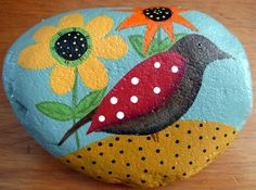 The beautiful folk art bird is painted on a background of soft aqua and surrounded with flowers of orange and yellow Sunflowers and Daisies. The colors are just gorgeous! The design is handpainted with acrylics onto a nice flat large river rock approximately the size of a flattened