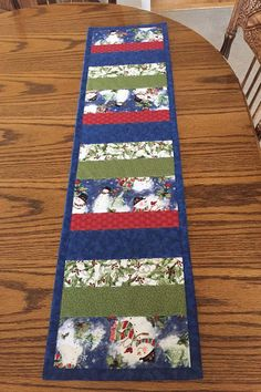 Add some color to your Winter or Christmas table with this quilted snowman table runner. This table runner is a perfect addition to your dining table, entry table, coffee table or dresser. Made with 100% cotton quilting fabrics. The runner measures approximately 10 x 39, and is