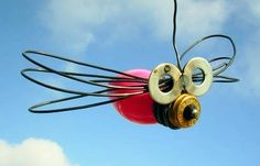 Glass Christmas Light bulb made in to a dragonfly bug using old and found items and old wire welded to make this great little bug !