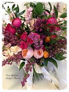Bridal bouquet of garden roses, heather, stock and ranunculus.