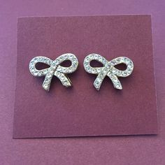 Cute Bow Earrings Silver colored Stud bow earrings dotted with gems. Includes both backs. Very in style! Jewelry Earrings