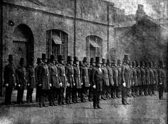 Manchester City Police peelers parade in the yard of the city's Albert Street Police Staion in the 1850s. Early police officers wore top hats and frock coats to allay public fears that the new forces were part of the military.