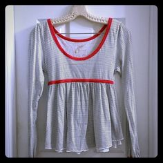 Free people top Free people striped top with red trim.  Has a red tie for the back to make it fitted against your body.  Still unsure if I want to sell, I was always hoping to wear it in Paris.  Yes, I am so clich?,  and even more clich?  for using the word.  Very cute. Free People Tops