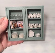"""Dollhouse Miniature Artisan Wall Cabinet FILLED =  This is filled (permanently) with glasses, dinnerware, serving dishes and cookbooks.  It is painted in a very light green color. The doors are plexiglass and in excellent condition.  It measures 4"""" in height, 4-1/4"""" wide and 1"""" deep. Z"""