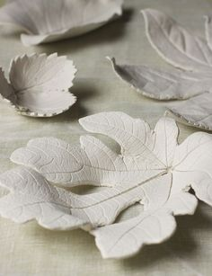 DIY clay leaves, maybe add a tealite candle to the center?  We could paint them blue or leave them a nice neutral color to help break up the table space?
