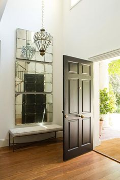two story foyer features a faceted lantern illuminating stacked antiqued mirrors over a bench alongside a black front door with brass hardware.