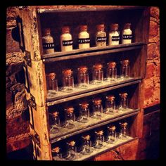 DIY sand collection display. Antique utility drawers hinged together with glass corked vials and embossed labels.
