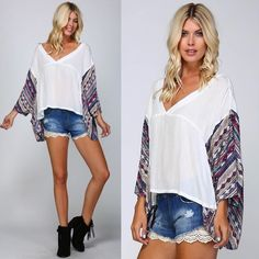 """GENEVIEVE Ethnic print kimono top - IVORY • Woven kimono top • Contrast ethnic print on kimono sleeves and lower back • Cut slightly longer in back • 2 small pockets in front • Wide V-neck • 100% cotton • Model is 5` 10"""" 34B-24-34 and wearing a size Small Fabric 100% cotton NO TRADE, PRICE FIRM also available in TAUPE Bellanblue Tops Blouses"""