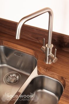 The contrast of a black American walnut worktop's dark tones with a modern undermounted sink and tap fitting is a very popular combination in modern kitchens. Consider bright white cabinets and other stainless-steel fittings for a clean, modern look.