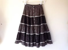 This sweet Gunne Sax skirt is made out of two black cotton calicoes printed with tiny pink, purple and white flowers, with lace and satin
