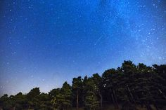 Two Perseid meteors (center & lower left) streak across the sky outside Madrid. Photo by Andres Kudacki