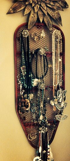 """Spray painted & repurposed a table-top ironing board into a jewelry """"organizer"""" using vintages glass pulls & hooks...crowned it with metal wall art...it works for me."""