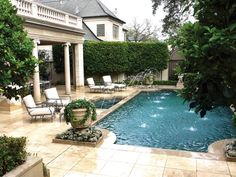 The extravagant courtyard features a Grecian style pool with water features splashing into the sides and connected to a hot tub. Large shrubs and trees act as privacy walls, while a dining area is covered by the second story patio. Comfortable lounge seating is poolside.