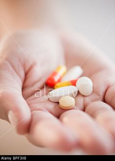 Hand holding pills and capsules © Blend Images / Alamy
