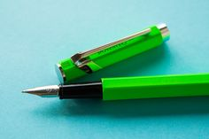 A flat lay of lime green and neon themed pens, fountain pens, notebooks, and ink.