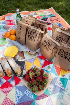Picnic reception at farm wedding with modern paper lunch bags on top of a patchwork quilt.
