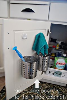 Ikea bins added to the inside of one side of the cabinet doors under the kitchen or bathroom sink. They're attached with mounting strips from the Dollar Store. I could also use my existing sink caddy!!