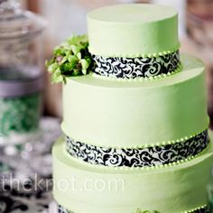 Katy and Bryan cut into a three-tiered cake iced with green buttercream and adorned with black-and-white damask ribbon. Elegant bunches of green orchids and hypericum berries mimicked the other floral details of the day.