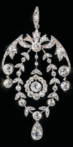 A BELLE EPOQUE PLATINUM AND DIAMOND PENDANT, CIRCA 1910. Designed as an millegrain-set old-cut diamond openwork foliate top with diamond single stone drops suspending a diamond articulated garland frame with central diamond two stone drop and rose-cut diamond detail, the centre with diamond cluster drop, to a platinum fine neckchain, with optional detachable brooch fitting, 7.5cm. #BelleÉpoque #pendant