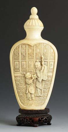 """Carved Ivory Snuff Bottle. Flattened spade form flask, carved with scholar & boy on one side and attendant & lady on reverse. Stopper glued on. Ht. 4 3/4"""""""