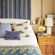 An antique Persian jajim textile hangs behind this bed, which is dressed with a simple white quilt and a mix of accent pillows.