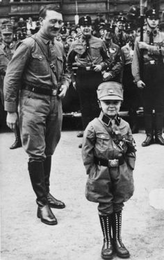An amused Hitler and SA troopers look upon a little German boy dressed as a National Socialist Party Stormtrooper during a national event.