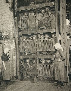 Circa 1900. Belgian Coal Miners  Coal miners ascend from the bowels of the earth in a multi-platform elevator.  Looks as scary as a D-ticket carnival ride.