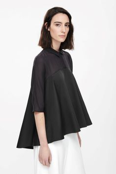 This tunic-style top, with a partial button fastening, is made from crisp cotton with a contrasting sheer panel along the shoulders. Flaring towards a graduated hemline, it has a narrow pointed collar, dropped shoulder seams and neat half sleeves.