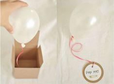 Invitación con globo, utilizando una cajita kraft y una cuerda podéis añadir la cuerda al globo y hacer que cuando se abra la caja el globo hinchado con helio salga hacia arriba con la etiqueta y el mensaje que vosotros deséeis escrito en ella.