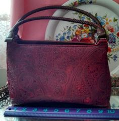 """Rich maroon color Relic handbag. Three interior compartments, one with smaller zipper compartment and the other has an eyeglass/key section. Middle section zips closed. All compartments come together with snap closure. """"Relic"""" tag inside. Exterior faux leather with paisley scroll work accented in black. Brown handles have braided texture, has """"Relic"""" hang tag. Brown faux leather grain bottom. 