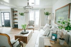 """he walls were painted with """"Amazing Grey."""" Chip and Jo also installed new lighting, trim, and nail down Pine hardwood flooring in the living room."""