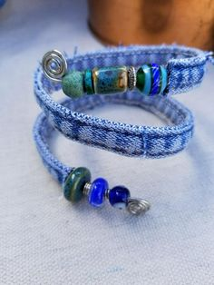 Using the inseam from a pair of recycled denim jeans, I have created a beautiful one of a kind bracelet. All of my recycled denim bracelets are handmade by inserting wire into the inseam or hem of jeans. This bracelet is adjustable but best fits wrists around 6 - 8. The bracelet is stiffened with 16