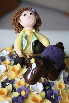 This is the 60th birthday cake I made for my friend's mum. A little horse and rider standing in a field of purple and yellow spring flowers with a few daffodills. This pic shows detail of the horse and rider.