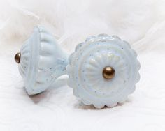 Large baby blue, ceramic knobs with antiqued brass hardware. Sweet Shabby Chic!