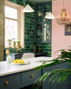 The kitchen of mydreams featuring pink walls, a gorgeous vintage chandelier, green tile, and tons of natural light.