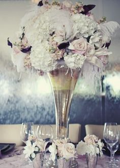 a mixture of white hydrangea, lilies, peonies, spray roses, blush roses, dark purple mini calla lilies, pink stock, and large gorgeous gardenias to create the old Hollywood vintage glam look. She accented these beautiful pieces with white ostrich feather plumes and tied the bouquet with a vintage sequin trim to complete the look