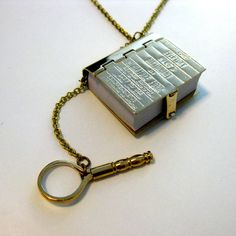 Dictionary Necklace -  fully operational miniature dictionary is lavishly bound in solid brass, with an intricately engraved front cover and comes complete with a mini-microscope for spellchecking whilst on the go. be still oh my beating heart