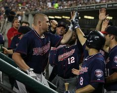 Chris Parmelee #27 of the Minnesota Twins high-fives teammates in the dugout after hitting a homerun in the fifth inning during a MLB game against the Detroit Tigers and the at Comerica Park on July 4, 2012 in Detroit, Michigan