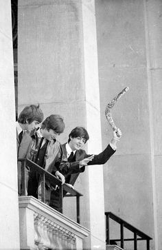 @hardtosayno | Paul McCartney waves a boomerang on the balcony of the Town Hall as John Lennon and George Harrison look down at the fans.
