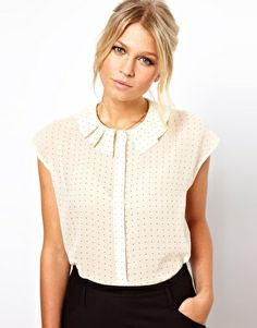 Round neckline with an origami collar on white blouse with black polka dots
