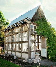 hmmmmm.... what would it take to build this one, 24 windows all about the same size, left over 2x12s and 2x4s, a door, half dz sheets of tin, and old siding for the bottom... and lots of hubby time. :)