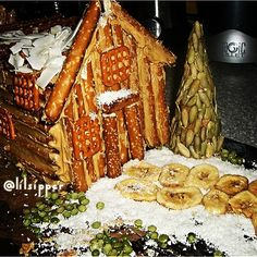"""A log cabin HEALTHY """"gingerbread"""" house. I used to make these out if graham crackers, frosting, and candy galore! The tree is made from a sugar cone, then I placed raw pumpkin seeds with honey as the """"glue"""". Coconut for the snow Split peas for the scarce grass popping through PB for the glue in between the pretzels Banana chips for the walkway"""