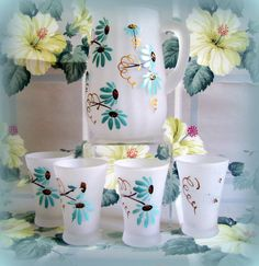 Vintage Mid Century Frosted Hand Painted Juice Pitcher and 4 Glasses Aqua Blue Daisies. $29.00, via Etsy.