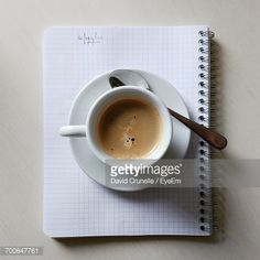 Stockfoto : High Angle View Of Coffee Cup In Plate On Spiral Notebook Over Table