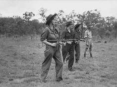 AWAS with Owen guns. Members of the Australian Women'€™s Army Service being instructed in the use of the Owen gun at Belmont in Queensland. From left to right: Lance Bombardier Lorna Molloy, Gunner Francis Fowler, Gunner Pamela Holden, instructor Warrant Officer Gilbert Page. Circa 1942 ~