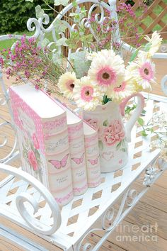 This shabby chic white metal seat, vase of flowers and coordinating covered books would look beautiful in a large hallway
